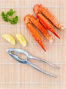 Boiled crab claws with lime and parsley on bamboo background. Stock Photos