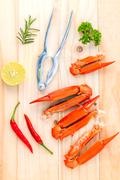Boiled crab claws with lime,chilli ,garlic and parsley on wooden background. Stock Photos