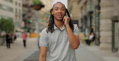 Young African American Black Asian mixed man walking talking cell phone Stock Footage