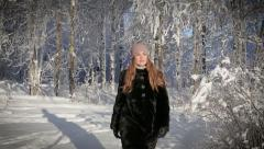 A beautiful woman is happy and walks in the park on a winter day. Stock Footage