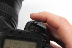 Finger is near the trigger button is digital camera close up Stock Photos