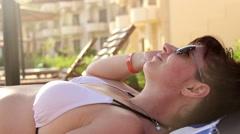 Woman In Bikini Tanning By The Pool, Enjoying Vacation, Wears Sunglasses - stock footage