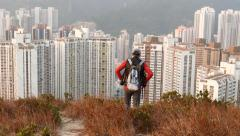 Hiker look down high hill edge, stand against massive dormitory blocks area. Stock Footage