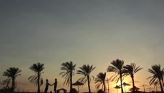 Silhouette Of A Loving Couple Under the Palm At Sunset Embrace and Kiss Stock Footage
