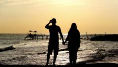 Silhouette Man and Woman Near the Sea at Sunset Stock Footage