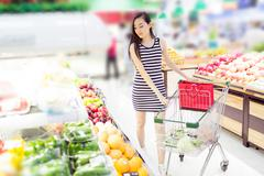 Stock Photo of chinese girl in the selection of fruit