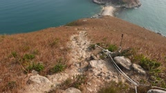 Steep path lie downhill, sea shore and small island seen below Stock Footage