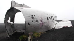 Crashed aircraft over lava field, dolly camera back Stock Footage