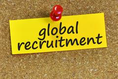 global recruitment word on yellow notepaper with cork background - stock photo