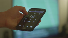 Controlling TV with Smart Phone - stock footage
