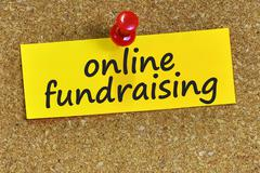 Online fundraising word on yellow notepaper with cork background Stock Photos