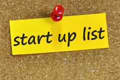 start up list word on yellow notepaper with cork background - stock photo