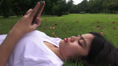 HD Format : Young woman lying on the grass and sending sms, texting in the park. Stock Footage