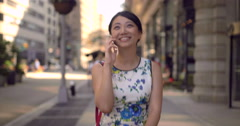Young Asian woman walking talking on cell phone slow motion - stock footage