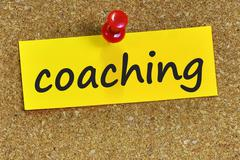 coaching word on yellow notepaper with cork background - stock photo