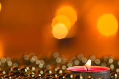 Burning candle and Christmas ornaments with bokeh in the background Stock Photos