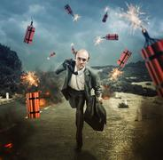 Man escaping from dynamite exploding Stock Photos
