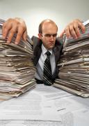 Businessman with big piles of paperwork Stock Photos