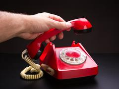 Red telephone handset in hand Stock Photos