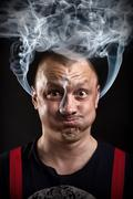 Stressed man with waving smoke from ears - stock photo