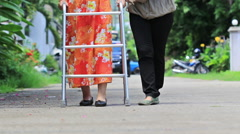Senior woman using a walker cross street Stock Footage
