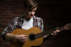 Attractive young guitarist playing acoustic guitar Stock Photos