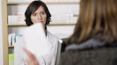 Concerned female pharmacist listening to a patient - stock footage