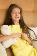 Stock Photo of little girl crying on a chair