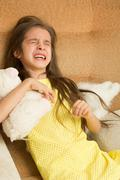 Little girl crying on a chair Stock Photos