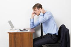 Frustrated office worker on the phone. holding neck Stock Photos