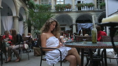 Young girl sitting on the summer terrace cafe and uses tablet Stock Footage