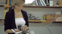 Attractive Business Woman reading magazine in modern office Stock Footage