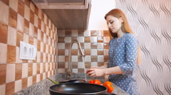 Healthy food lifestyle: beautiful woman casually cooking, washing vegetables at Stock Footage