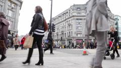 Shoppers pass to and fro in London's busy Oxford Circus Stock Footage