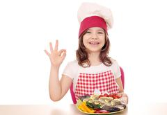 Happy little girl cook with trout and ok hand sign Stock Photos