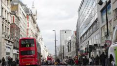 Buses, taxis and people pass in different directions on Oxford Street Stock Footage