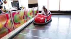 Emirati parents with children riding bumper car at funfair. Stock Footage