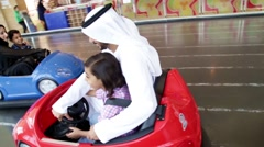 Stock Video Footage of Parents with children riding bumper car at funfair.