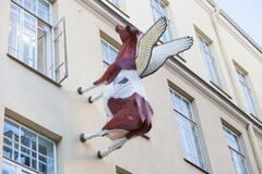 Cow sculpture on the wall of the house Stock Photos