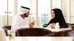 Emirati couple taking selfie using mobile camera at restaurant. Stock Footage