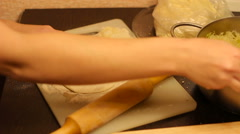 Rolling out dough with a rolling pin in hand - stock footage