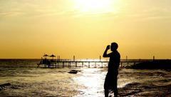 Man wears sunglasses near the sea at sunset Stock Footage