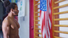 4K Professional male gymnast training on wall bars with American flag. - stock footage