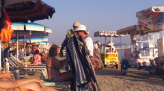 Clothes' Merchants hope to sell their goods on the beach Stock Footage