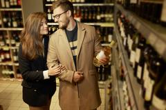Couple choosing alcohol in a liquor store Kuvituskuvat