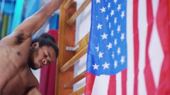 4K Professional male gymnast training on wall bars with American flag. Stock Footage