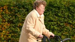 Old lady walking with wheel walker in autumn park  Stock Footage