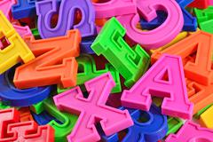 Heap of plastic colored alphabet letters close up - stock photo