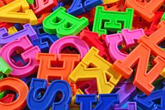 Heap of plastic colored alphabet letters close up Stock Photos