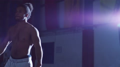4K Professional male gymnast practicing flips & turns in dark gym - stock footage